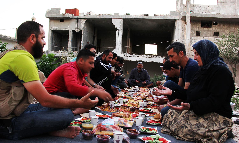 Syrians break their fast in the middle of destroyed buildings in Teir Maalah, north of Homs, during Ramazan on June 16, 2016. ─ AFP