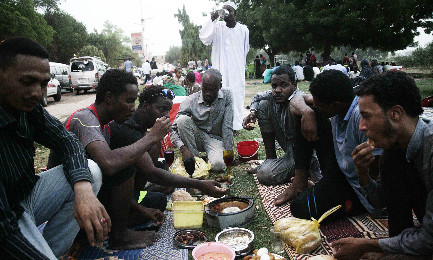 Sudanese share a picnic at a park on Nile Street as they break the fast on June 17, 2016 in the capital Khartoum. ─ AFP