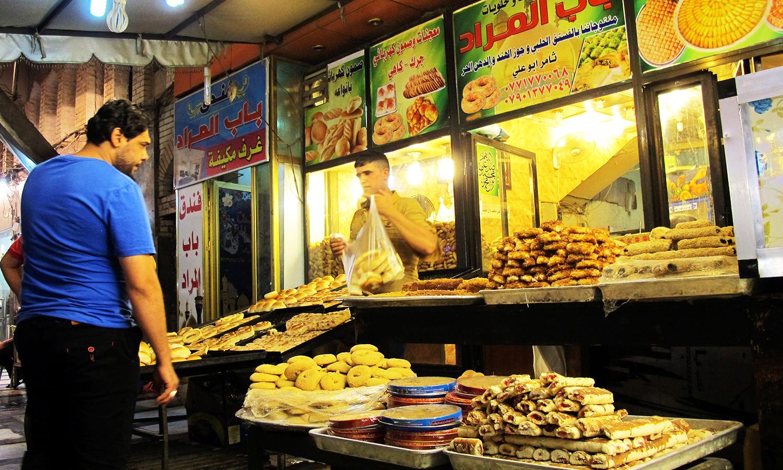 An Iraqi man buys bread at a shop during Ramazan on June 17, 2016 in Kadhimiya, a northern neighbourhood of Baghdad. ─ AFP