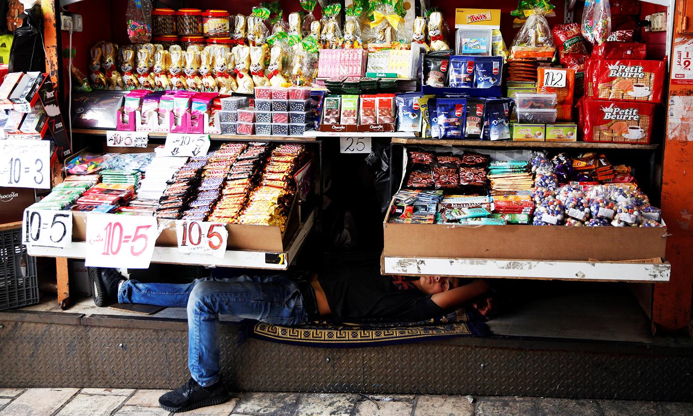 A Palestinian vendor rests inside his shop in Jerusalem's Old City June 17, 2016. ─ Reuters