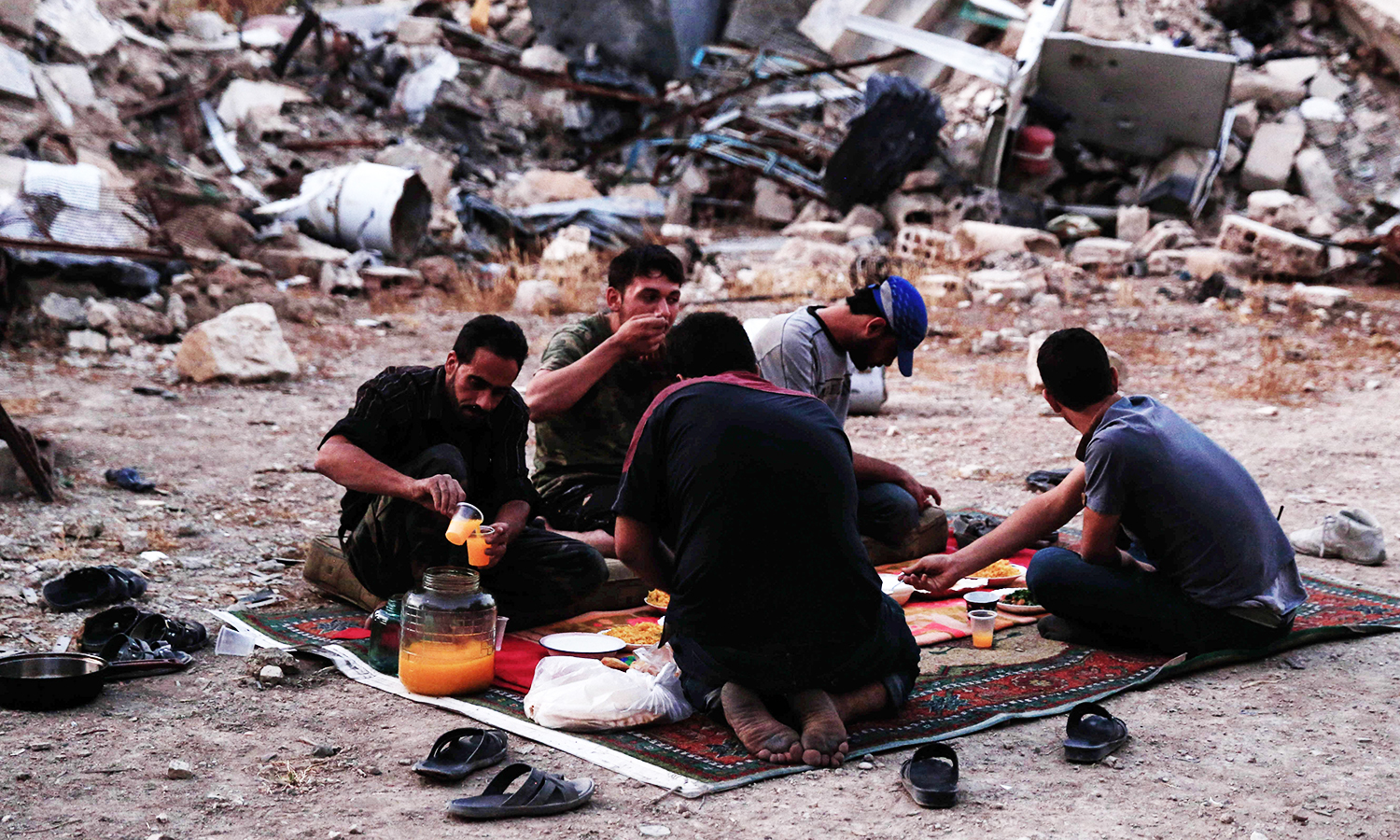 Fighters from the Free Syrian Army sit in front of detroyed buildings as they prepare to break their fast during Ramazan on June 16, 2016 in the rebel-held neighbourhood of Jobar, on the eastern outskirts of the capital Damascus. ─ AFP