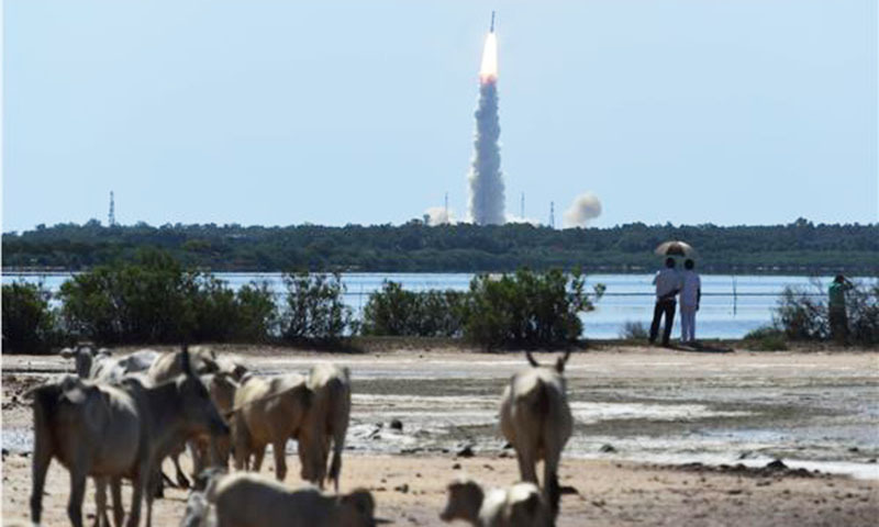 Bystanders watch as the ISRO satellite is launched. ─ AFP