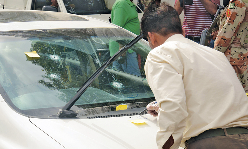 A crime-scene expert inspects the bullet-riddled car of Amjad Sabri after the attack.—Photo by White Star