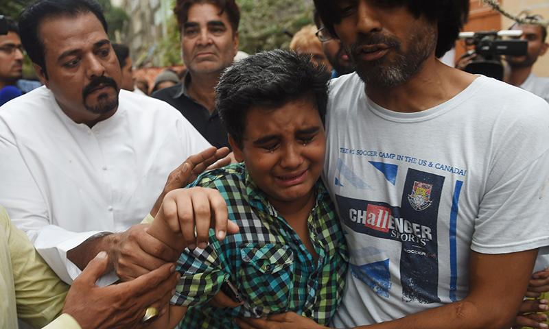 Relatives comfort Mujjudid Sabri (C), Amjad Sabri's son. ─ AFP