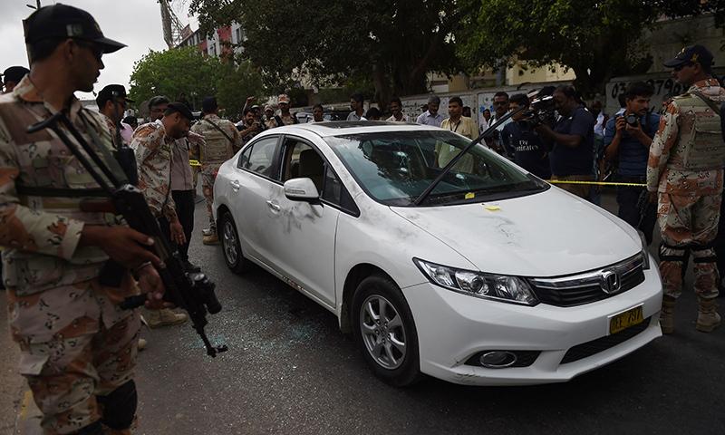 Rangers personnel inspect Amjad Sabri's bullet-riddled car. ─ AFP