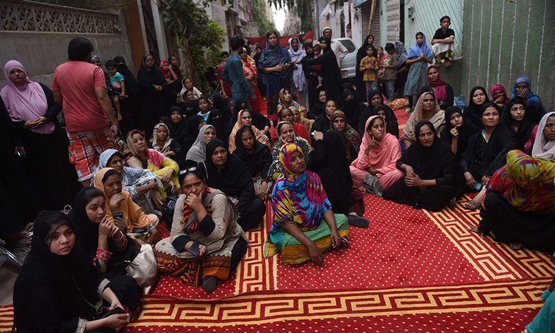 People gather outside Amjad Sabri's house after the attack on the qawwal. ─ AFP