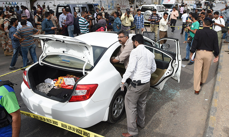 Security officials inspect Amjad Sabri's car. ─ AFP