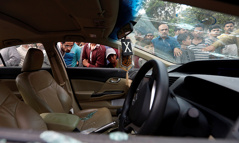 Onlookers look into the car driven by Amjad Sabri. ─ Reuters