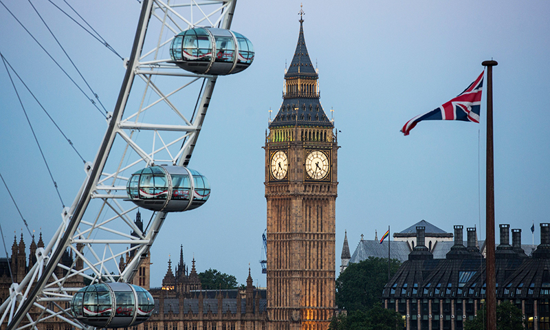 A Union flag flies beside the London Eye in front of the Queen Elizabeth Tower (Big Ben) and The Houses of Parliament  in London on June 24, 2016. — AFP