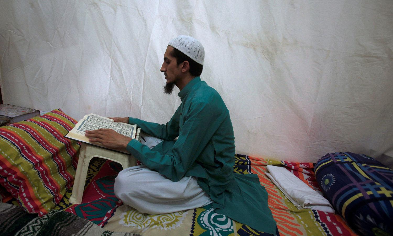 ایک شخص پشاور کی ایک مسجد میں اعتکاف میں بیٹھنے کے بعد قرآن مجید کی تلاوت کررہا ہے — رائٹرز فوٹو