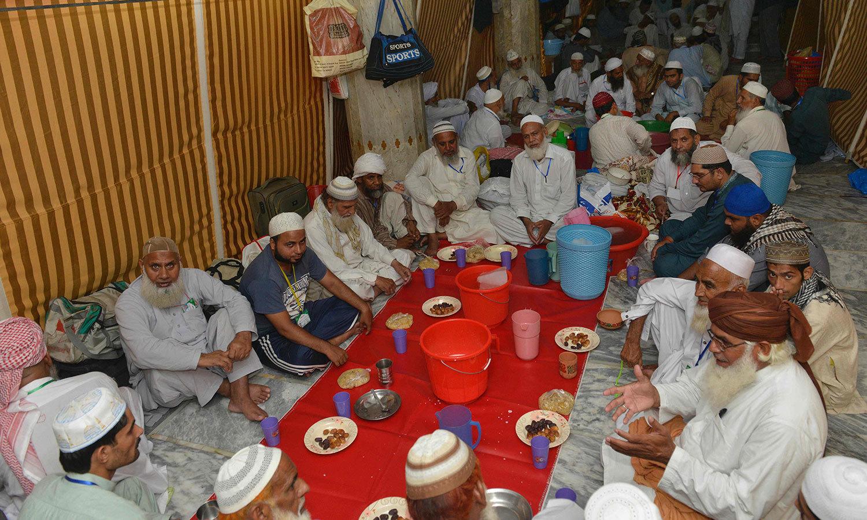 لاہور کی ایک مسجد میں اعتکاف کے لیے جمع ہونے والے افراد روزہ افطار کررہے ہیں — اے ایف پی فوٹو