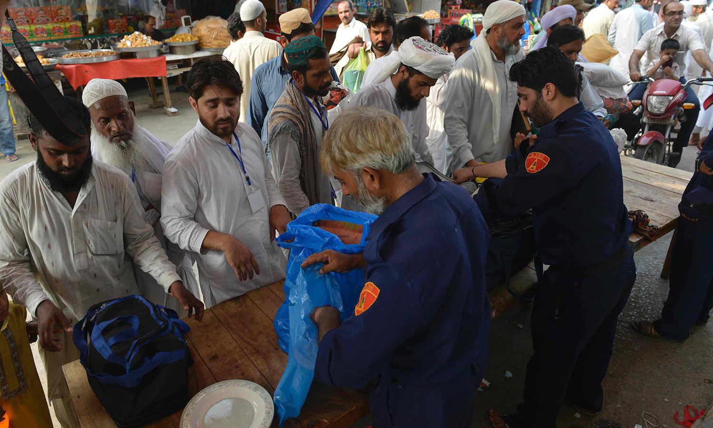 لاہور میں ایک مسجد میں اعتکاف کے آغاز سے قبل سیکیورٹی گارڈز لوگوں کا سامان چیک کررہے ہیں — اے ایف پی فوٹو