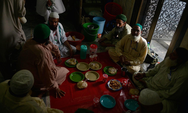 لاہور کی ایک مسجد میں متعکفین روزہ افطار کرتے ہوئے — اے ایف پی فوٹو