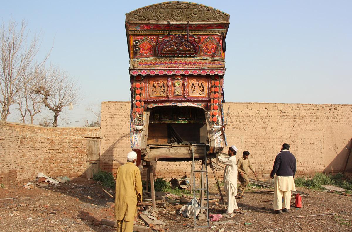Laborers repair the body of a truck in Peshawar