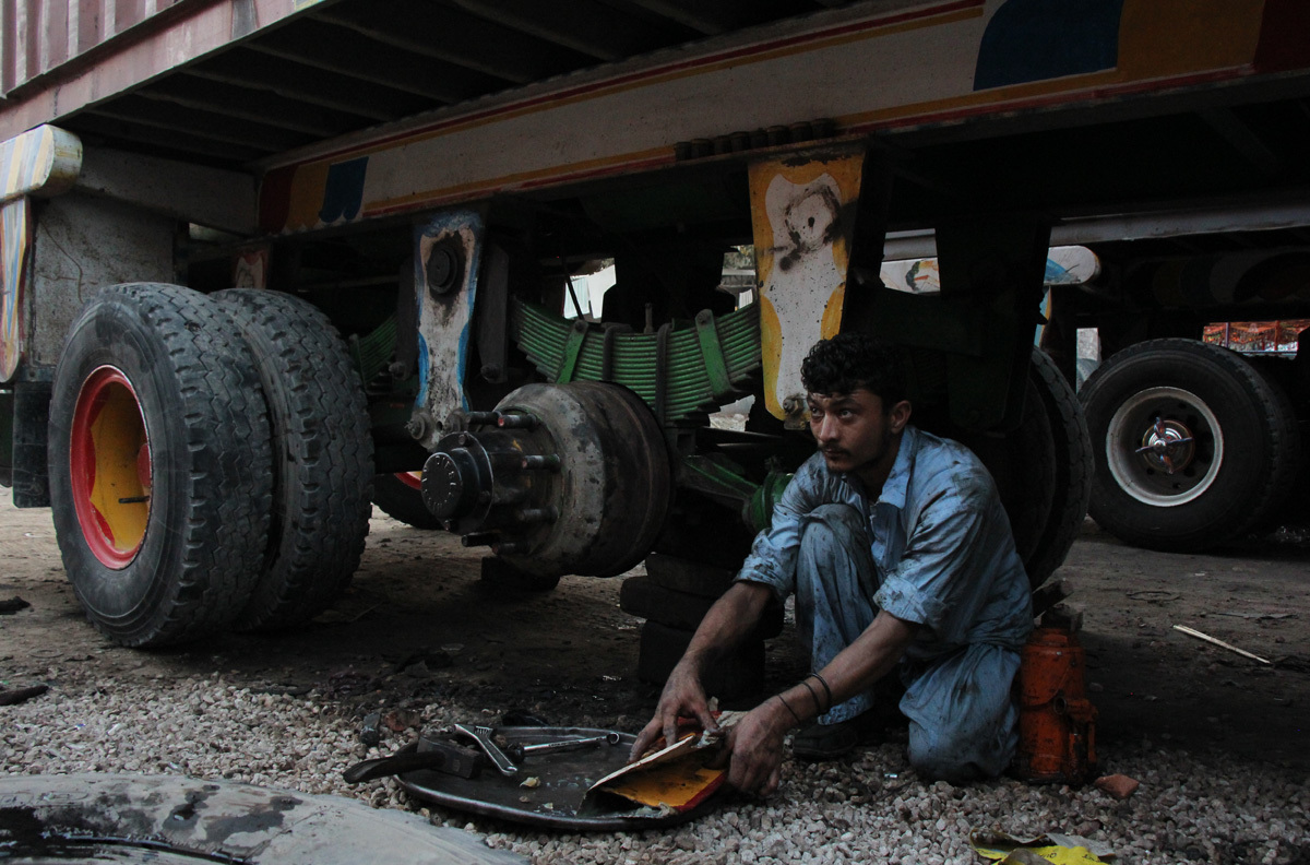 A mechanic works on a truck in Mirpur Khas