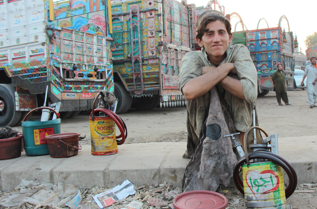A young mechanic sits on the roadside in Hyderabad's truck adda