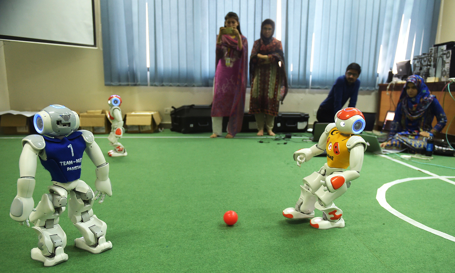 Students and team members of Robotics and Intelligence Systems Engineering (RISE) watch as their robot football players take part in a match at the engineering department of NUST in Islamabad. — AFP
