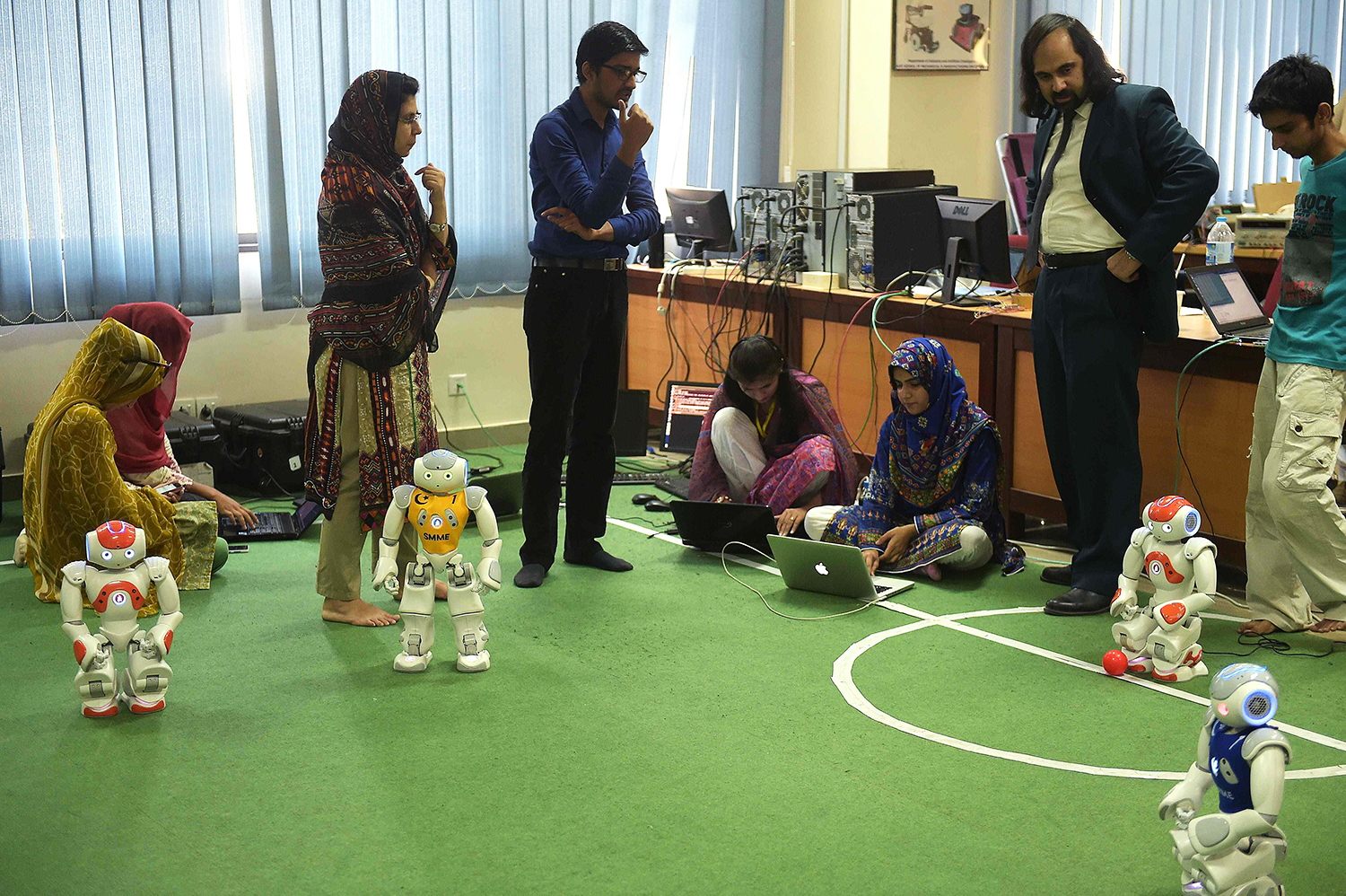 Students and team members of Robotics and Intelligence Systems Engineering (RISE) programme their robot football players. — AFP