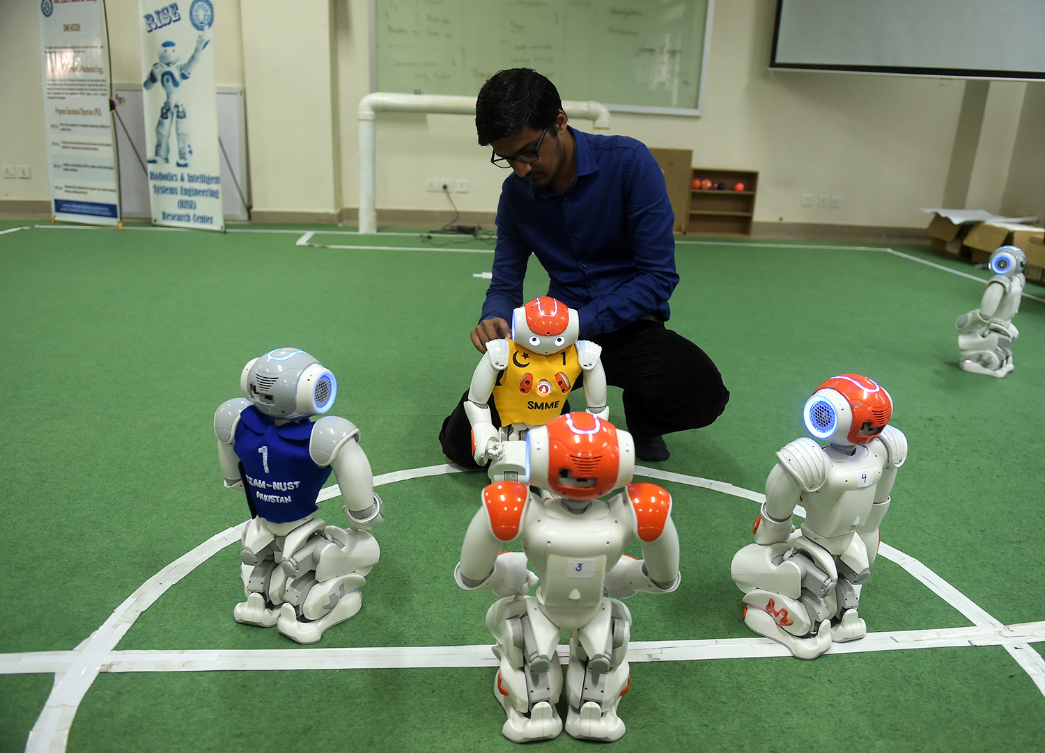 A student and team member of Robotics and Intelligence Systems Engineering (RISE) places robot football players on the pitch. — AFP