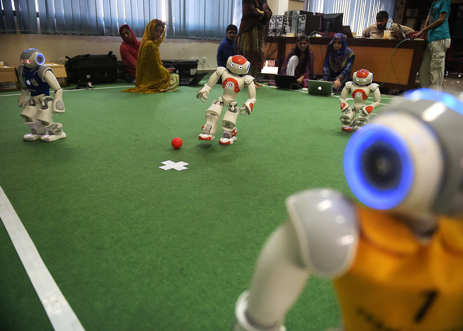Students and team members of Robotics and Intelligence Systems Engineering (RISE) watch as their robot football players take part in a match. — AFP