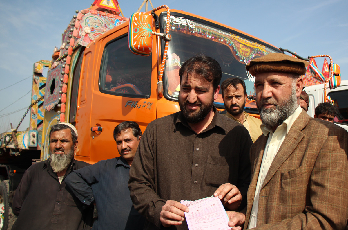 Ahmed Shinwari and his son hold a challan (ticket) that one of the drivers has received, Lahore