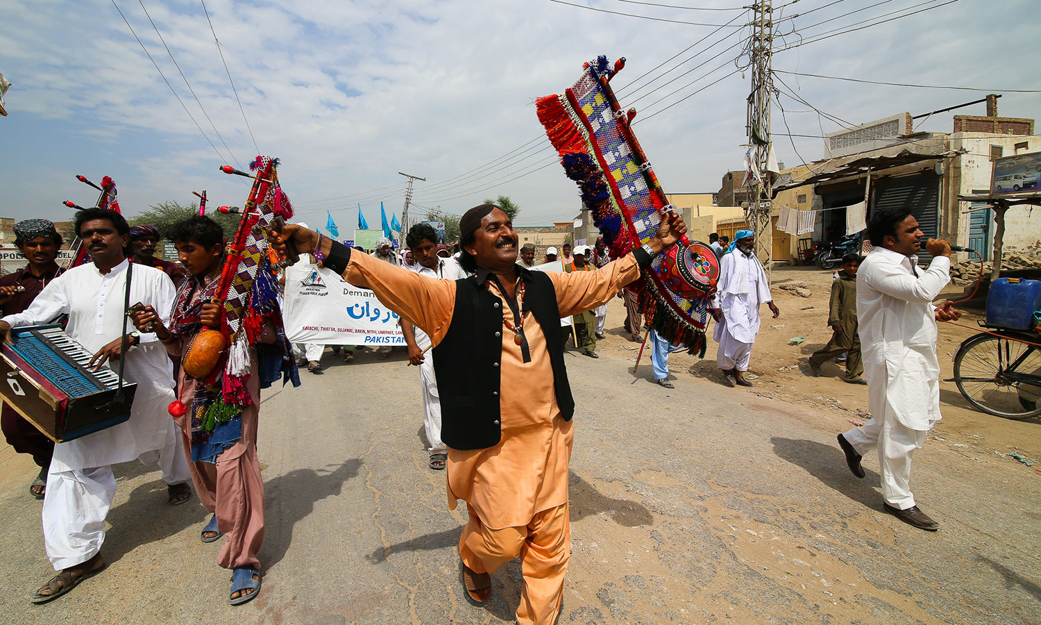 Maula Bux leads the caravan in song and music. The caravan has reached Sanghar City.