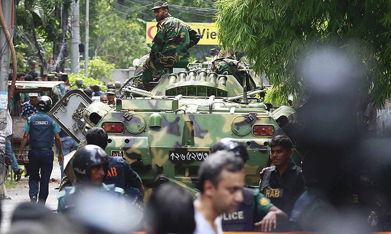 Bangladeshi soldiers and security personnel sit on top of armored vehicles as they cordon off an area near the sieged restaurant.— AP