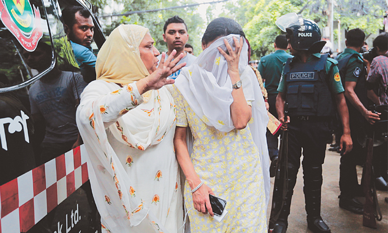 A relative on Saturday tries to console a Bangladeshi woman whose son was missing after militants killed hostages in the restaurant. ─ AP