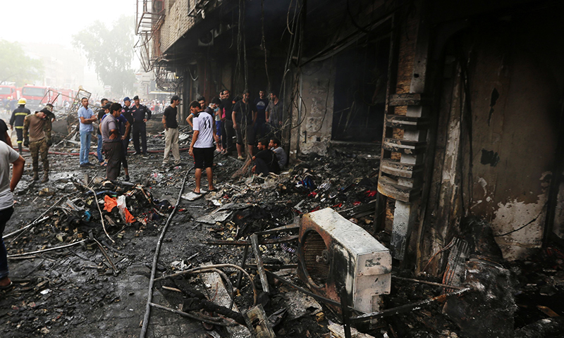 Iraqis inspect the damage at the site of a suicide car bombing claimed by the Islamic State group on July 3, 2016 in Baghdad's central Karrada district. ─ AFP