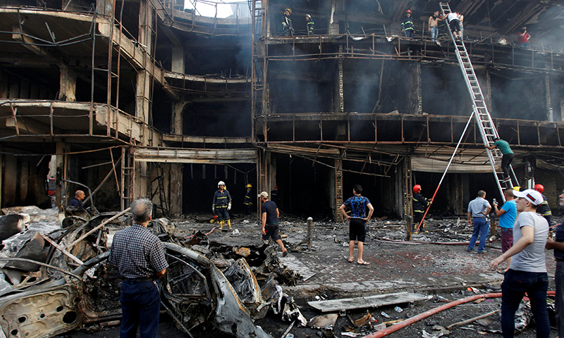 People gather at the site of a suicide car bomb in the Karrada shopping area, in Baghdad, Iraq July 3, 2016. ─ Reuters