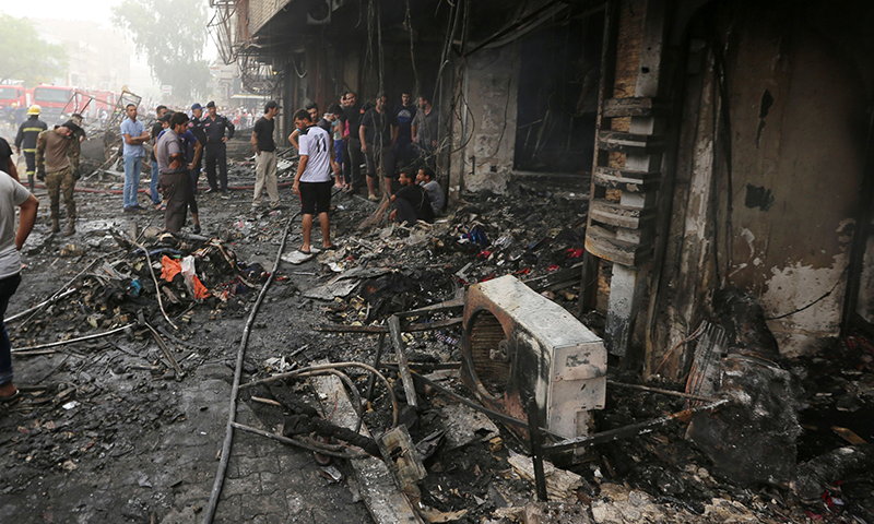 Iraqis inspect the damage at the site of a suicide car bombing claimed by the Islamic State group in Baghdad's central Karrada district. — AFP.