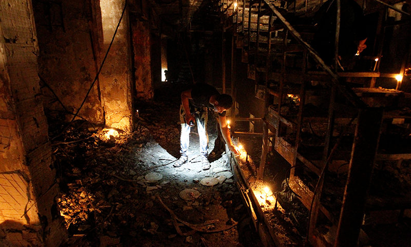 A man lights a candle at the site after a suicide bombing in the Karrada shopping area, in Baghdad, Iraq. — Reuters