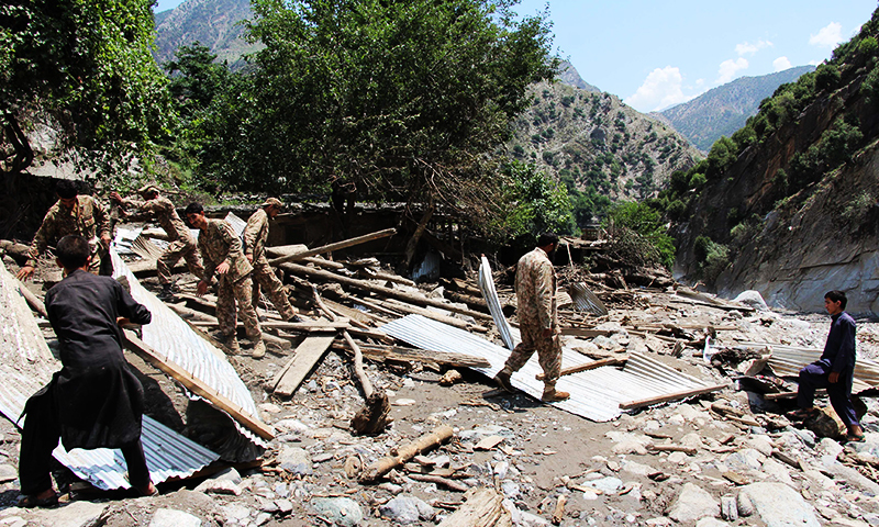 Pakistani army personnel help villagers after their house was destroyed by flash flooding in Ursoon village in Chitral on July 3, 2016. ─ AFP