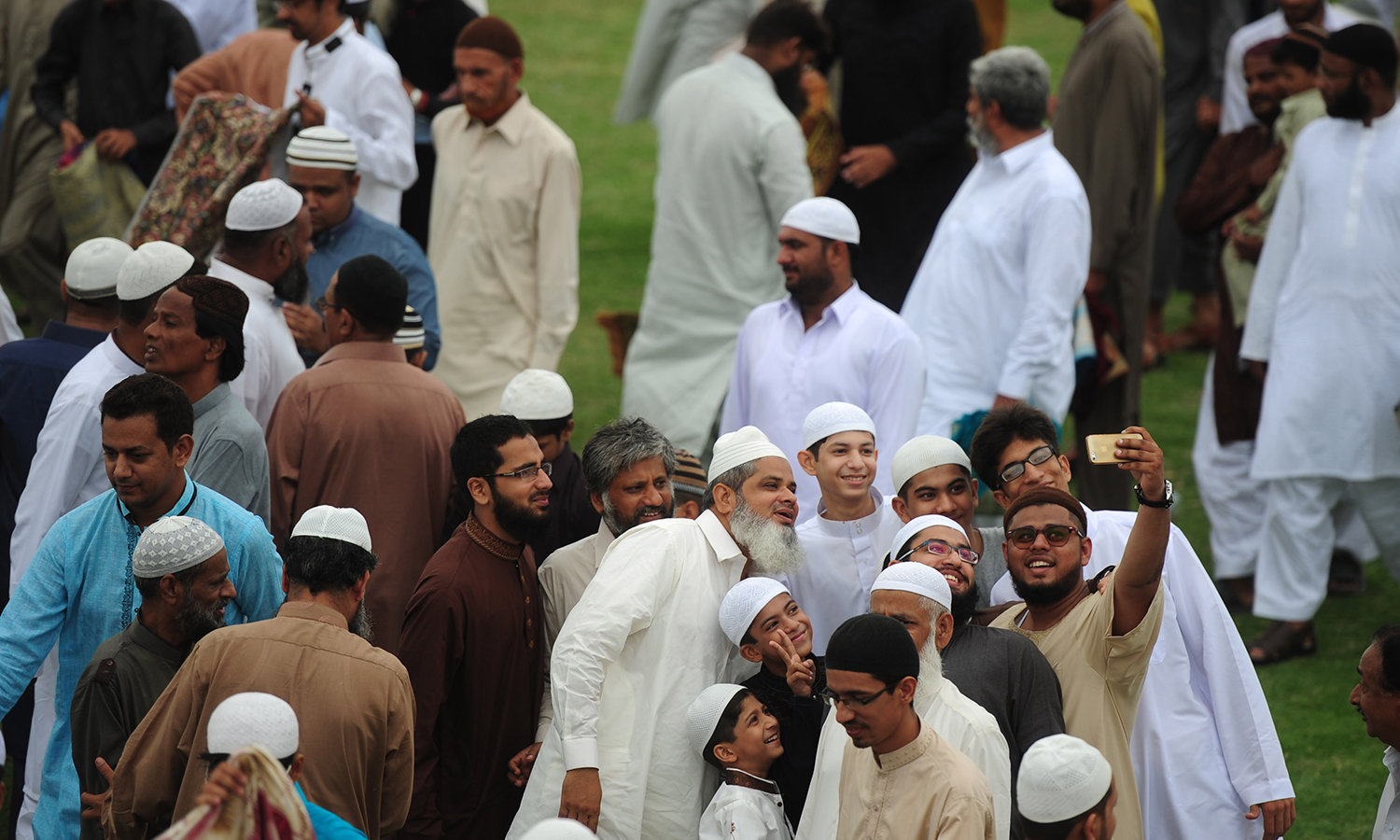 KARACHI: After the Eidul Fitr prayers, a group takes a selfie outside the mosque. — AFP/Asif Hassan