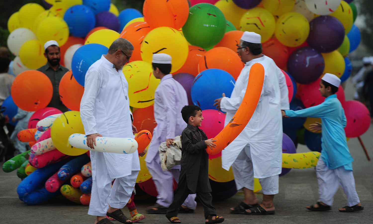 KARACHI: Children buy balloons after offering Eidul Fitr prayers at a mosque on Wednesday.  —AFP/Asif Hassan