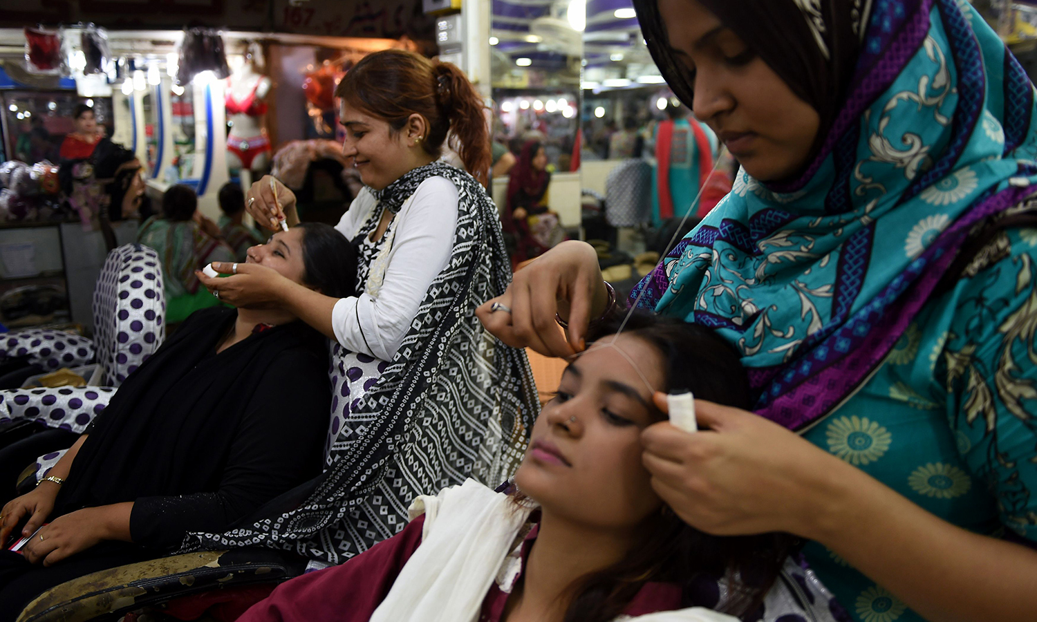 KARACHI: Women gather in beauty parlours to get their beauty regimens out of the way ahead of Eid. —AFP/Asif Hassan