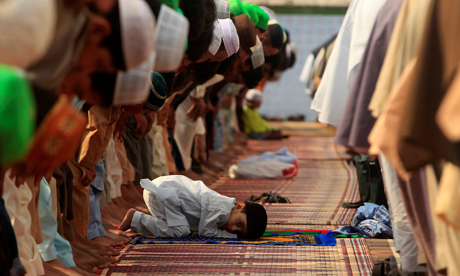 RAWALPINDI: A boy attends Eidul Fitr prayers with others at Jamia Masjid on Wednesday. —REUTERS/Faisal Mahmood