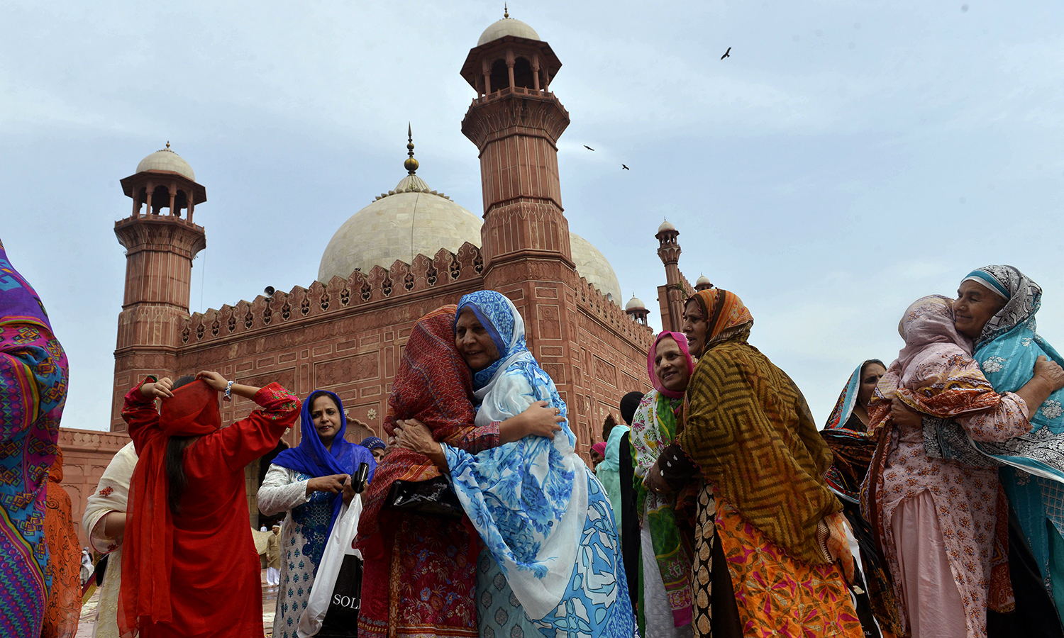 LAHORE: Women hug each other after offering the Eidul Fitr prayers at the Badshahi Masjid on Wednesday. —AFP /Arif Ali