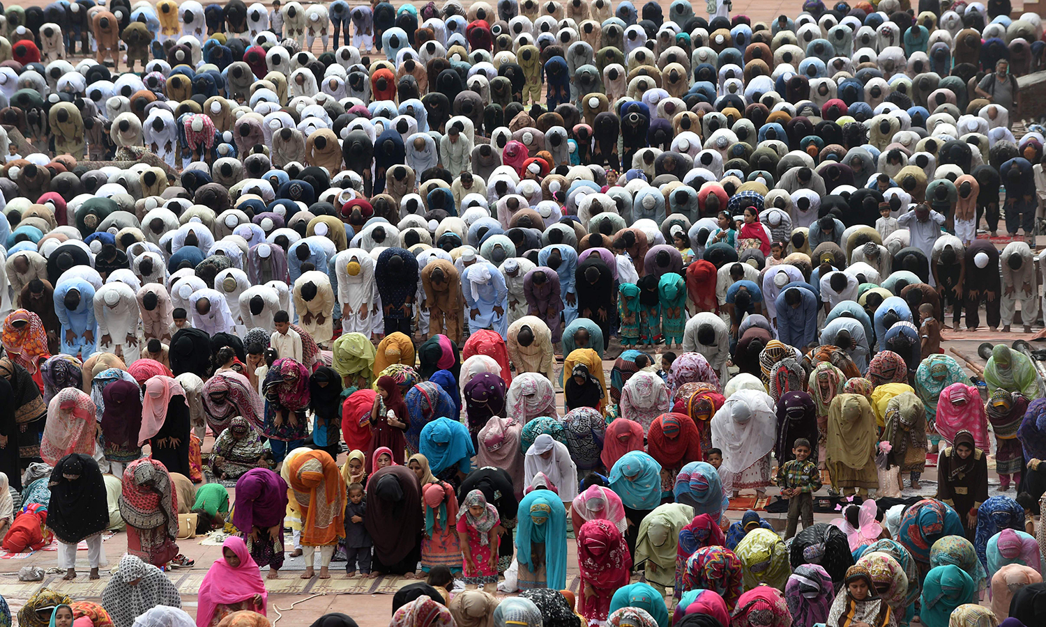 LAHORE: Men and women offer Eidul Fitr prayers at the Badshahi Masjid on Wednesday morning. —AFP/Arif Ali