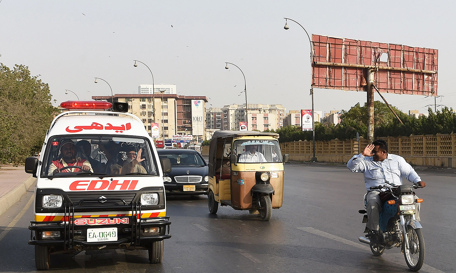 A Pakistani motorcyclist pays his respects to Abdul Sattar Edhi as he travels to his office in Karachi. —AFP