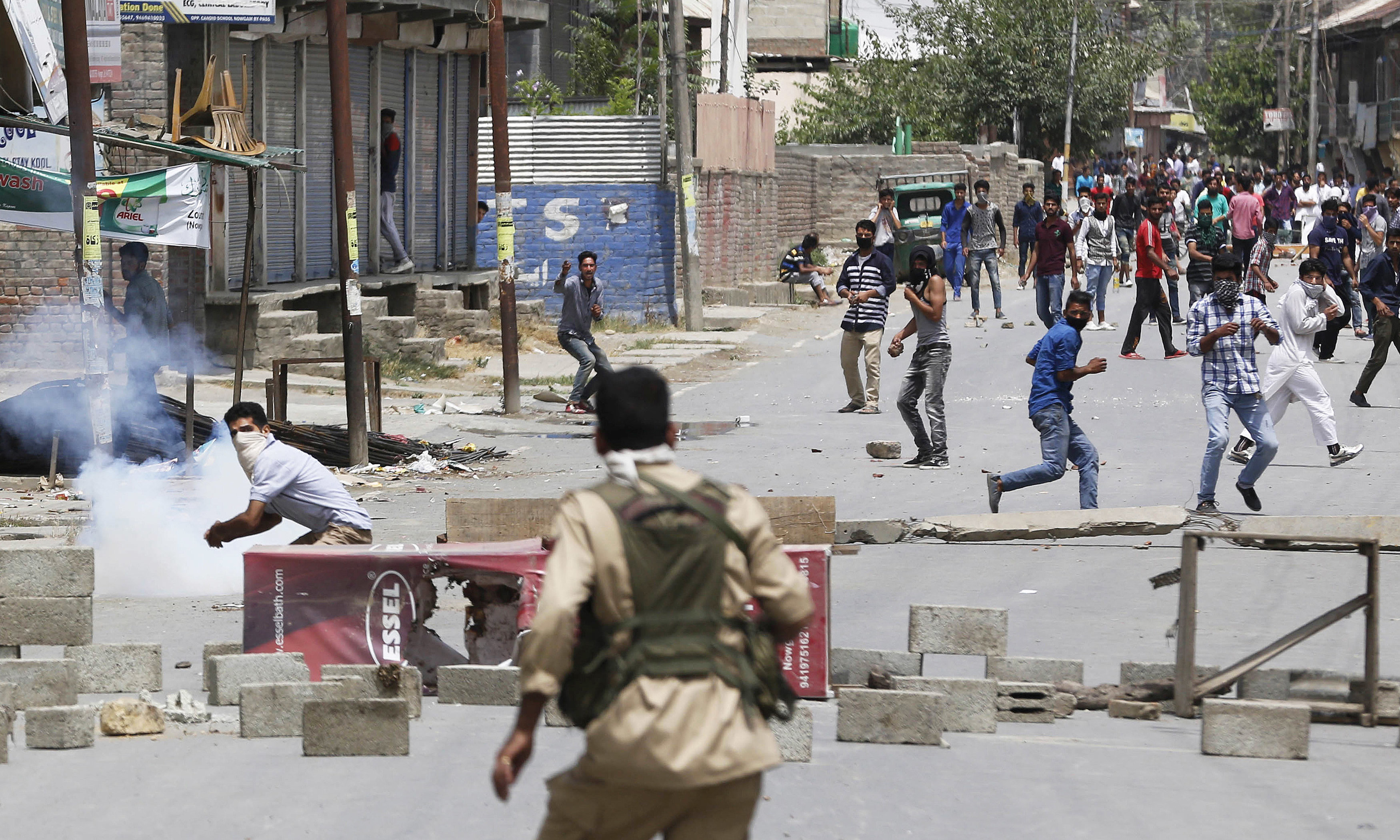A masked Kashmiri protester prepares to throws a brick at an Indian policeman during a protest in Srinagar.  —AP