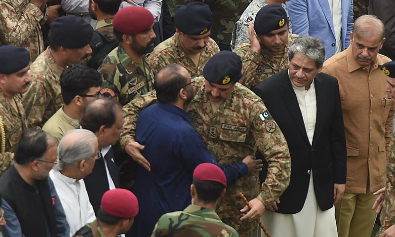 COAS Raheel Sharif hugs the son of Abdul Sattar Edhi, Faisal Edhi (C), during his father's funeral.─AFP