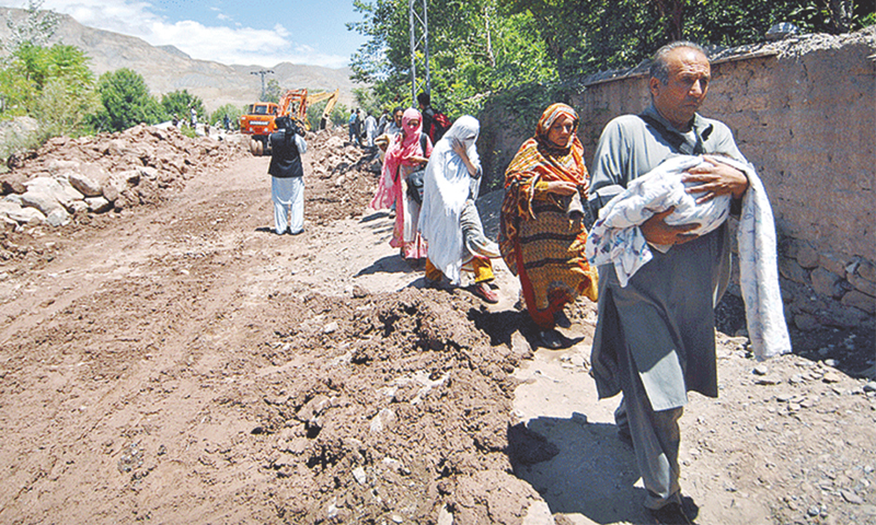 A family heading towards their destination while walking on a damaged road in last year's floods -File photo