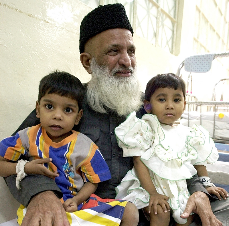 Abdul Sattar Edhi holds infants at Edhi Childcare Center in Karachi. —AP Photo