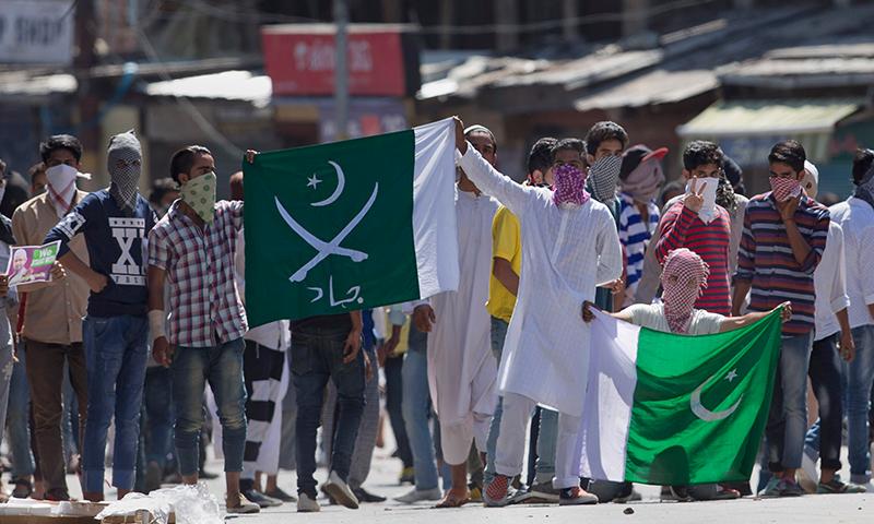 احتجاج کے دوران نوجوان  پاک فوج کے نشان اور پاکستان کے جھنڈے اٹھائے نظر آئے— فوٹو: اے پی