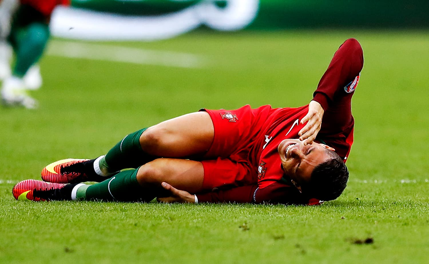 Portugal skipper Cristiano Ronaldo lies on the pitch in pain. — AP