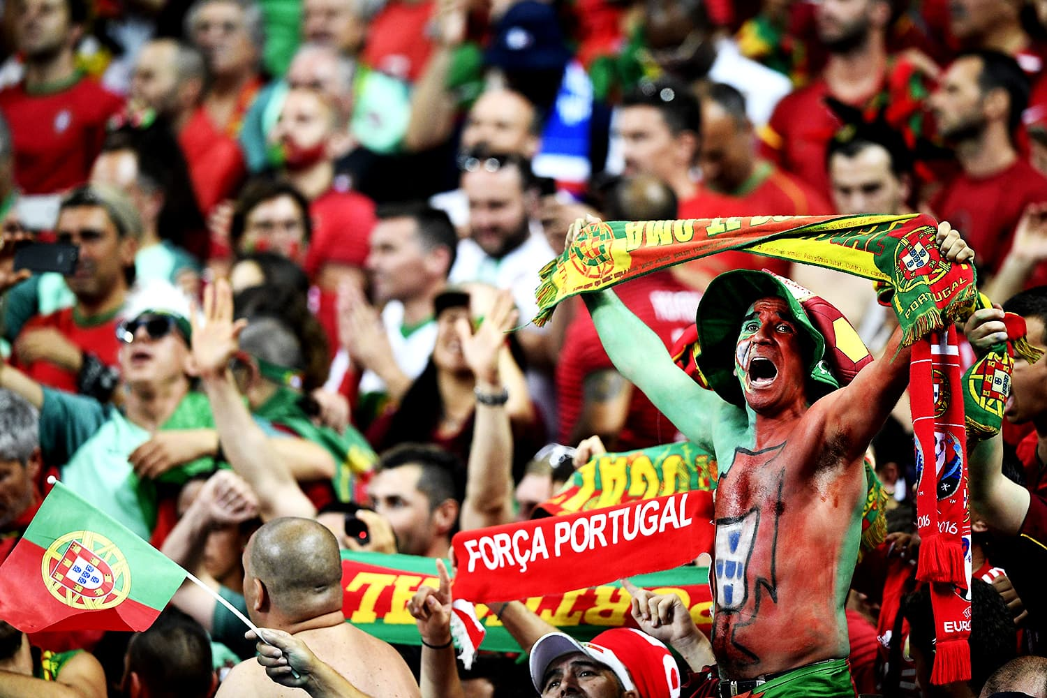 Portuguese fans, donned in their national colours, chant slogans to back their team. — AFP