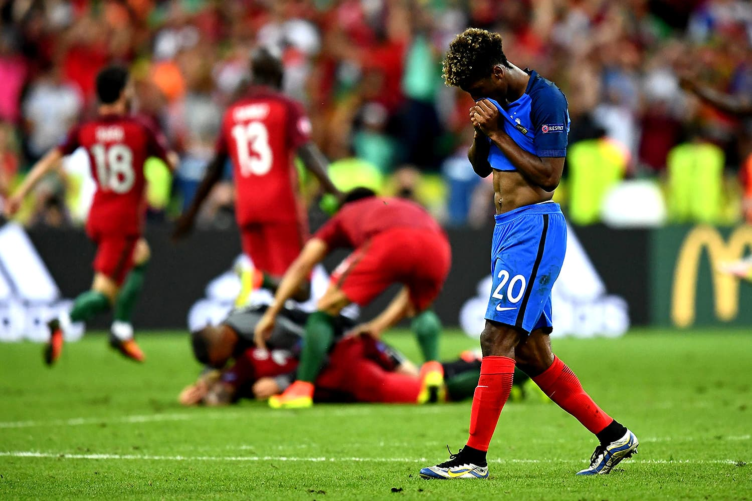 Kingsley Coman of France hides his face as Portugal players celebrate victory in the background. — AFP