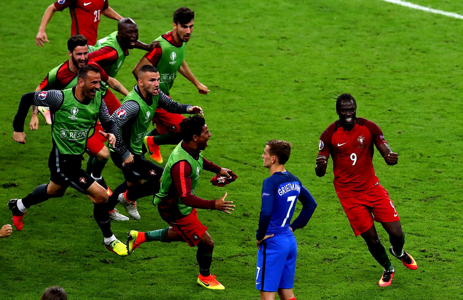 Portugal players run onto the pitch from the bench in celebration as France's Antoine Griezmann looks on. — AP