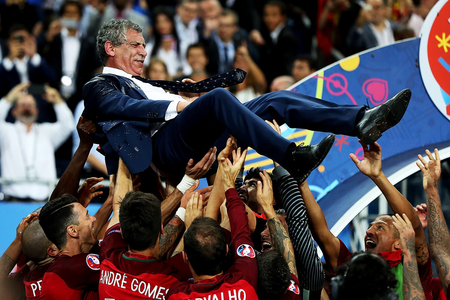 Portugal players toss their coach Fernando Santos up in the air in celebration. — AFP